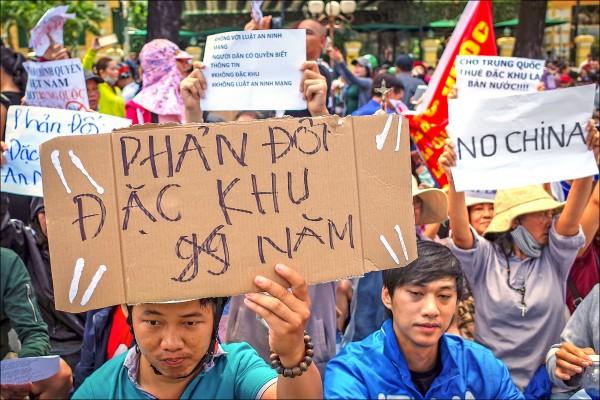 越南胡志明市街頭十日爆發反中示威,抗議者高舉「不要中國」等標語,反對可能圖利中資的「經濟特區法」草案。(歐新社)