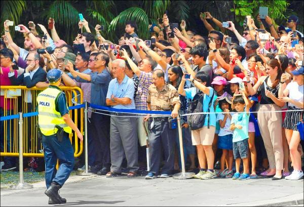 新加坡民眾舉起手機,等待從星國總統府離開的美國總統川普車隊出現。(美聯社)