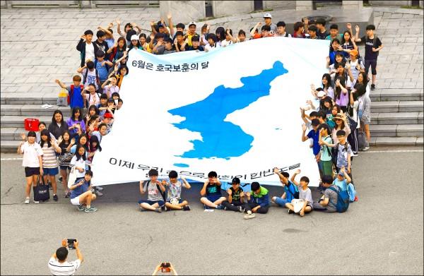 南韓學生十一日在鄰近兩韓非軍事區的京畿道坡州市臨津閣和平公園,拉起巨型朝鮮半島地圖,高呼「我們將親手創造朝鮮半島和平」。(法新社)
