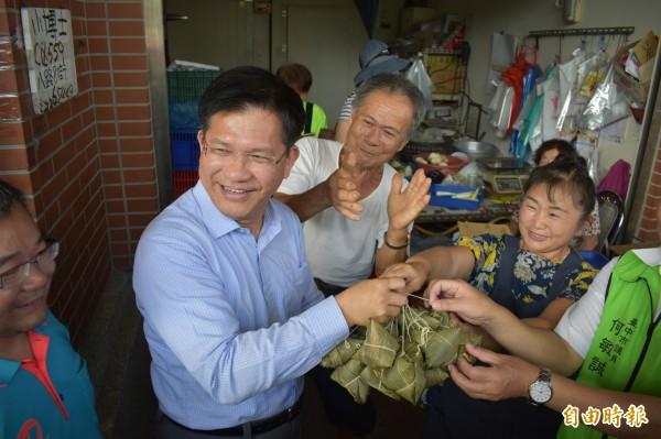 台中市長林佳龍今天巡視建國市場,攤商贈送象徵當選連任的粽子。(記者張瑞楨攝)