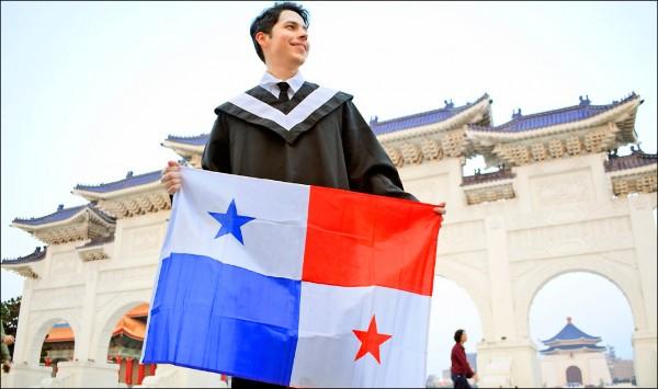 台巴斷交將滿一年,Eliécer Casasola等巴國留學生仍堅持在台念書,不打算轉赴中國。圖為Eliécer Casasola在自由廣場前攤開巴拿馬國旗。(Eliécer Casasola提供)