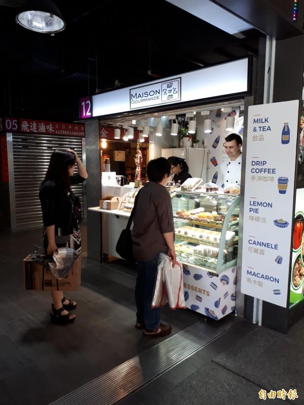 在叫賣聲此起彼落的台灣傳統市場裡,看見高大的法國主廚Loïs擺好攤位販售Maison gourmande手工法式糕點,相當吸睛。(記者蕭皓文攝)