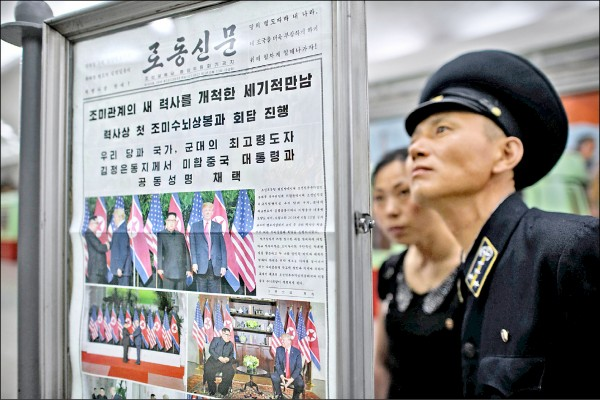 北韓民眾十三日在平壤地鐵站圍觀勞動黨黨報「勞動新聞」對「川金會」的報導。(法新社)