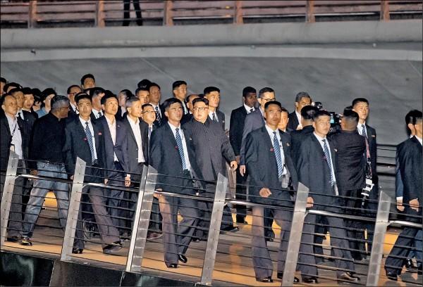 北韓領導人金正恩(中)十一日晚間離開下榻的新加坡瑞吉酒店,在星國官員陪同下夜遊星國知名景點濱海灣花園,大批護衛隨侍在側。(彭博)