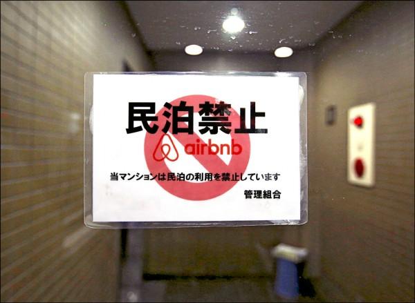日本東京一棟公寓大廈大門口張貼禁止經營民泊的告示。(路透)