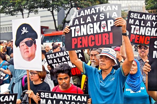 今年四月馬國民眾在首都吉隆坡發起抗議,他們高舉畫成海盜的劉特佐肖像,要求逮捕一馬弊案主謀劉特佐。(美聯社檔案照)