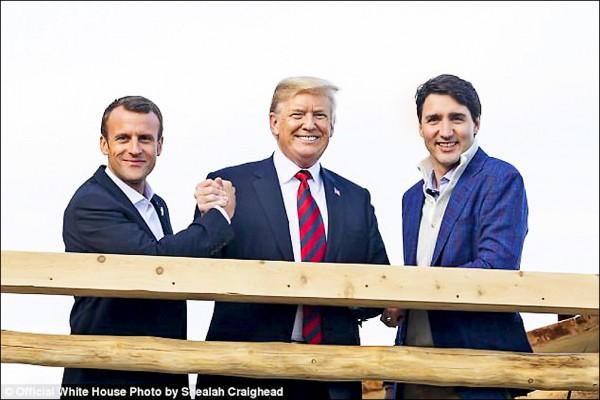 川普(中)也貼出批評他保護主義貿易政策的法國總統馬克宏(左)、加拿大總理杜魯道三人在露台上微笑的合照,尤其川、馬兩人的拳頭還緊扣,看來超「麻吉」。(取自川普推特)