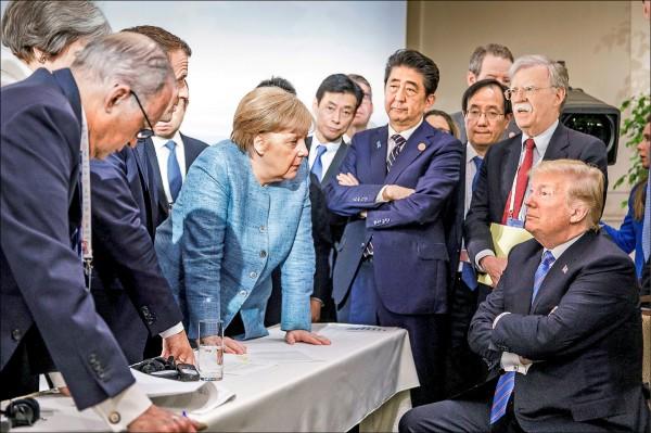 德國總理梅克爾(雙手撐桌者)此前發布一張七大工業國集團(G7)加拿大峰會九日開會時的照片,看似她睥睨美國總統川普(右一),且川普與圖左的幾位歐洲國家領袖針鋒相對。(路透)