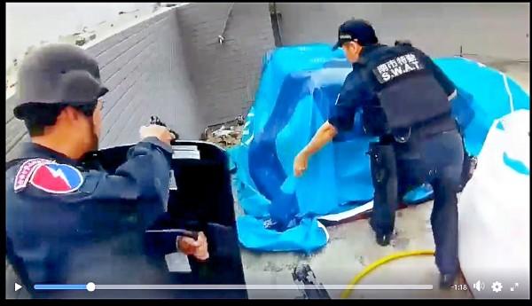 警方在一處施工中民宅六樓頂,逮獲躲在帆布內的楊嫌,起獲警槍與十一顆子彈。(記者王俊忠攝翻攝)