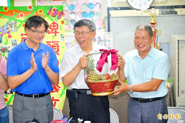 Taipei Mayor Ko Wen-je, second right, is yesterday presented with a pineapple and zongzi rice dumpling gift basket during a visit to Pitou District Borough Warden Lin Ming-ching, right, in Taipei's Zhongshan District.