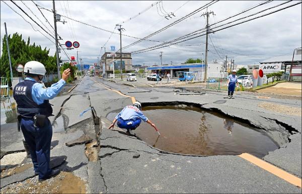 大阪十八日發生強震後,高槻市路面出現嚴重龜裂和坑洞,自來水管在破裂後湧出大量水。(法新社)