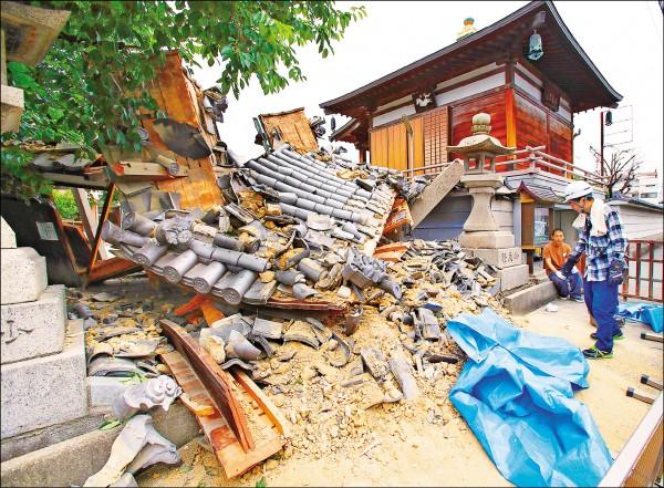 日本大阪北部十八日發生規模六‧一強震,大阪府茨木市妙德寺入口的山門崩塌,門柱的木材和屋瓦碎落一地。(美聯社)