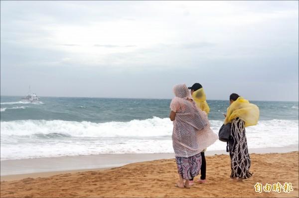 同團親友在沙灘上守候。(記者劉禹慶攝)