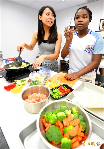 陽明大學期末考題讓醫學生親自下廚,將平時所學的醫學與營養知識,實際運用到菜色設計。圖為學生湯真(左)與史瓦帝尼交換生狄語謙(右)下廚料理。(記者劉信德攝)