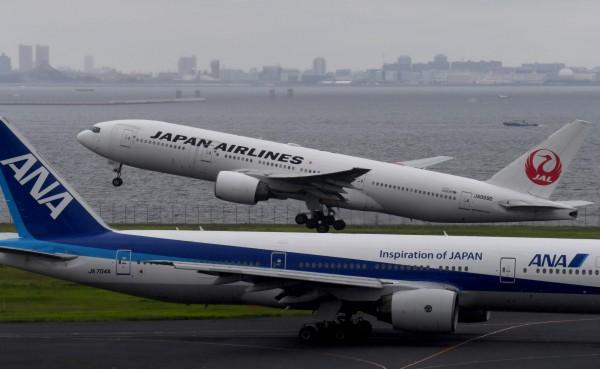 日航以及全日空只在簡體中文網頁變動台灣名稱,有外媒認為是面對中國壓力的可行辦法,可能有其他外國企業跟進。圖為日航班機(遠處)及全日空(近處)班機。(法新社)