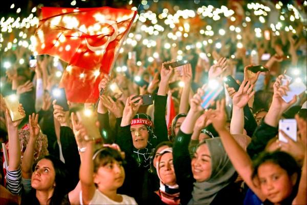 土耳其廿四日舉行總統暨國會二合一選舉,投票結束後,總統艾多根的支持者在安卡拉高舉土國國旗與執政黨「正義與發展黨」黨旗,並揮舞手機。(歐新社)