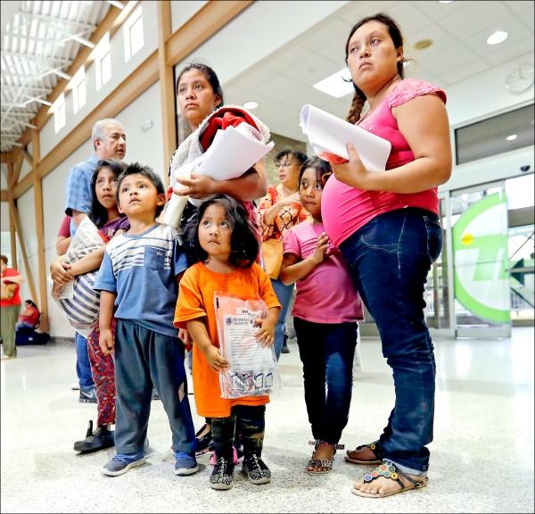 兩名來自瓜地馬拉的母親與她們的子女,二十四日獲美國海關暨邊境保護局釋放後,在德州麥卡倫的中央巴士站等候。(美聯社)