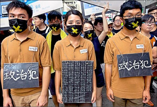 香港中文大學學生穿著囚衣,以及寫有118名政治犯名字的紙牌,聲援入獄的異議人士。(歐新社)