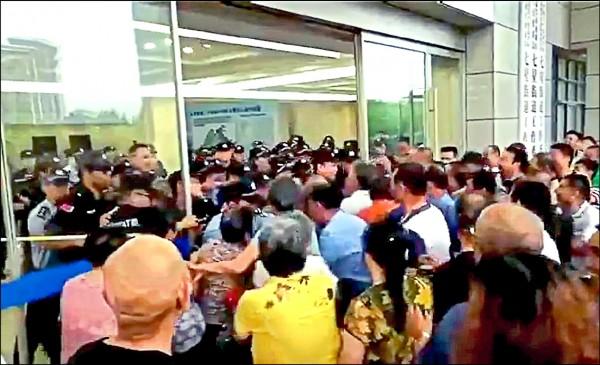 中國浙江嘉興市六月卅日爆發示威,不滿徵地措施的民眾包圍闖入政府大樓,拿磚石攻擊武警。(取自網路)