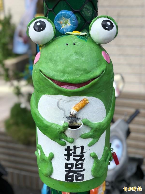 母蛙外型的「菸投器」,眼睛上方有眼睫毛,懸掛在燈桿上,相當吸睛。(記者湯世名攝)
