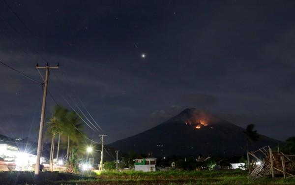 阿貢火山週一晚間9點多突然劇烈噴發,灼熱的熔岩流淌而下,經過之處冒出火光。(路透)