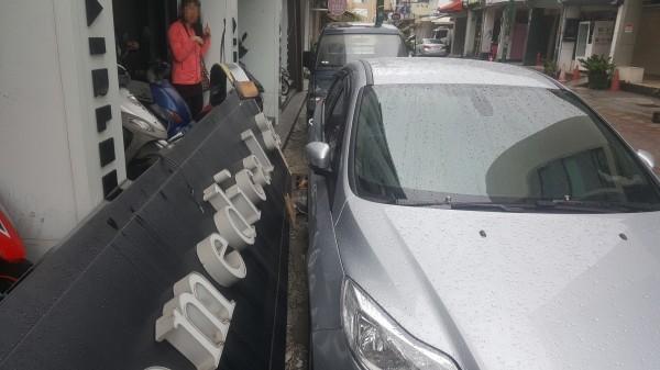 高雄連續2天大雨,商店招牌吹落砸毀轎車,車主要求償。(記者黃良傑翻攝)