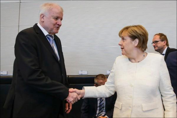 德國基社盟黨魁暨內政部長賽賀佛(左)二日與總理梅克爾(右)會晤後,雙方已就移民政策達成妥協協議,梅克爾暫逃下台命運。(美聯社)
