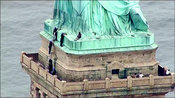 紐約市非裔婦女歐考姆(Therese Okoumou)在四日美國獨立紀念日當天,爬上紐約市地標自由女神像的基座,並與警方展開長達四小時的對峙。(法新社)
