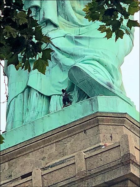 紐約市非裔婦女歐考姆(Therese Okoumou)在四日美國獨立紀念日當天,爬上紐約市地標自由女神像的基座。(路透)