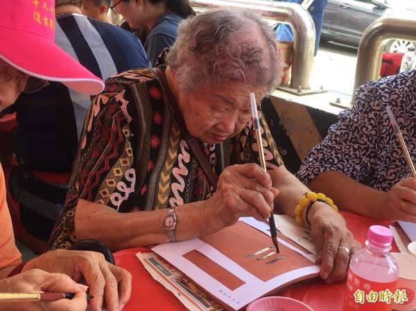 三芝94歲莊吳罕奶奶是千人揮毫活動最年長的參加者。(記者葉冠妤攝)
