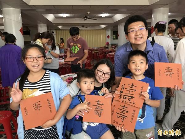 2歲的蔡明諺小弟弟(左二)在家人協助之下,也順利揮毫完成了「壽」字。(記者葉冠妤攝)