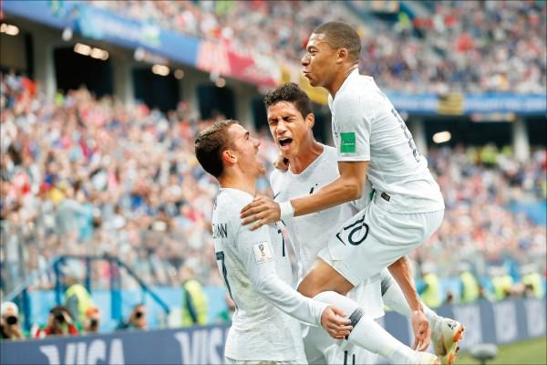 世足賽昨8強戰,上半場先由法國瓦拉內(中)頭錘破網先馳得點,下半場「小王子」葛里茲曼(左)長射再下一城,2:0力克烏拉圭。(美聯社)