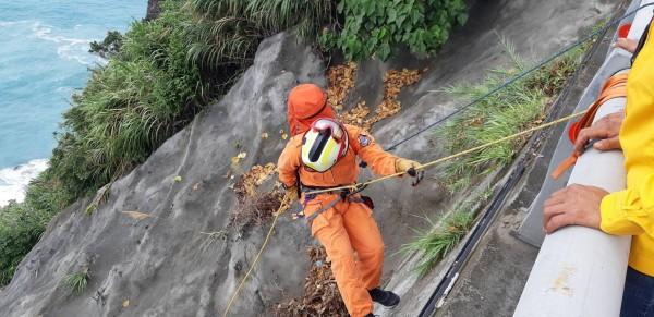 花蓮消防人員獲報後,立刻拉繩索下邊坡將受困一夜的李女救上路面。(記者王峻祺翻攝)