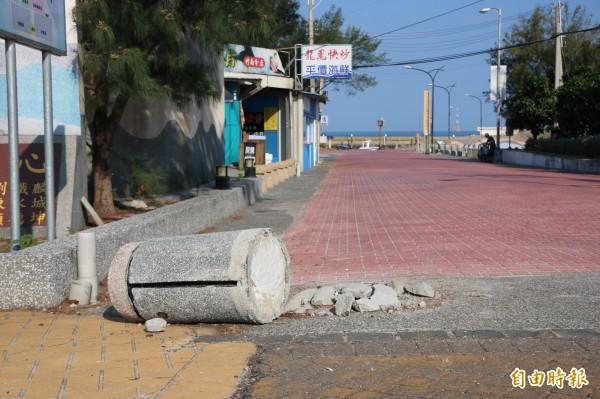 龍鳳漁港入口處的景觀石柱遭撞斷,一個月來卻擱置原地無人處理。(記者鄭名翔攝)