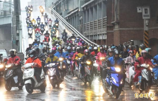 圖為不少新北市民今日冒雨騎車到正常上班上課的台北市工作,讓著名的「台北橋機車瀑布」依舊維持高峰的機車車流量。示意圖,與本新聞無關。(記者劉信德攝)