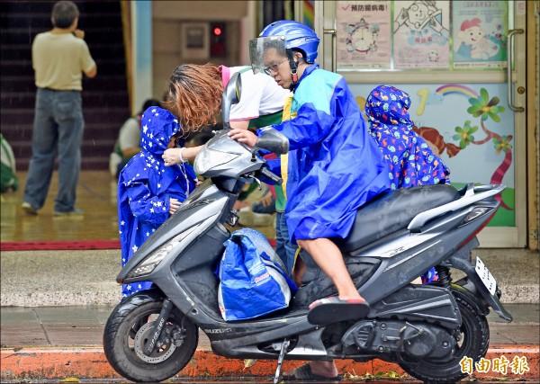 中颱瑪莉亞接觸北台灣,台北市11日未達停班停課標準,家長冒雨送孩子到幼稚園上課。(記者羅沛德攝)