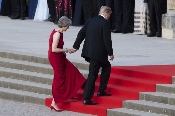 川普牽起梅伊的手,兩人一同走紅毯。(歐新社)