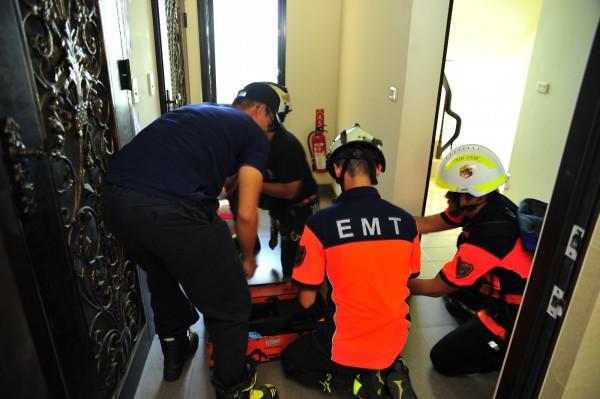 消防隊當機立斷悄聲破門。(記者王捷攝)