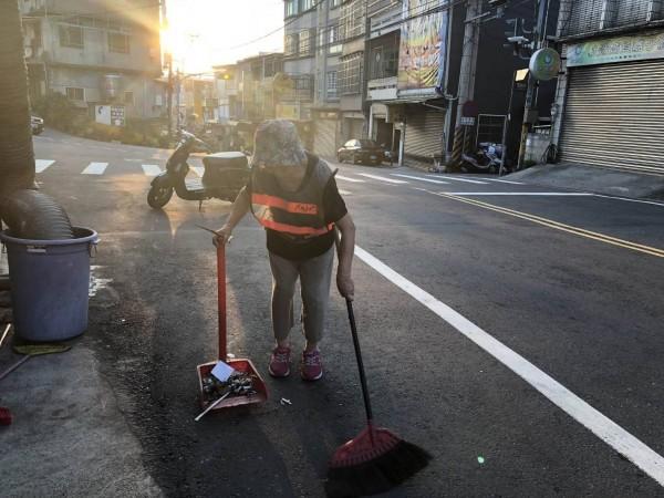 新竹縣寶山鄉68歲婦人何美惠,每天清晨自己默默低頭掃街,來回約兩公里,近20年來不曾間斷,許多人以為她是清潔隊員,封她為「寶新路的守護大使」!(林寶全提供)