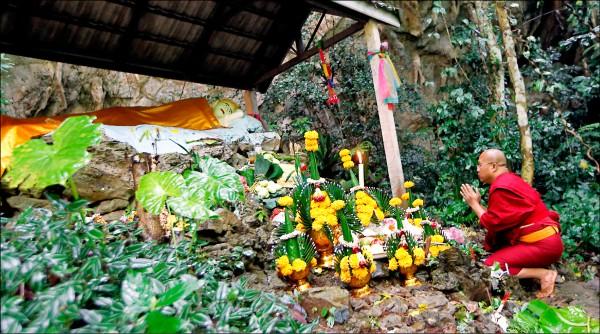 泰國足球隊少年受困洞穴初期,僧侶在洞穴外祈福。(美聯社檔案照)