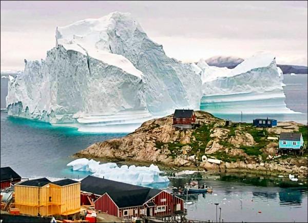 一座體積如小山丘的冰山,12日漂向格陵蘭西岸的伊納蘇特村(Innarsuit)海邊,並且卡在海床上。(美聯社)