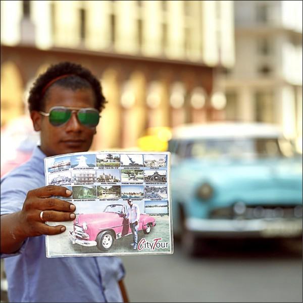 圖為一名古巴青年十四日在哈瓦那街頭向觀光客展示不同的行程報價。(歐新社)