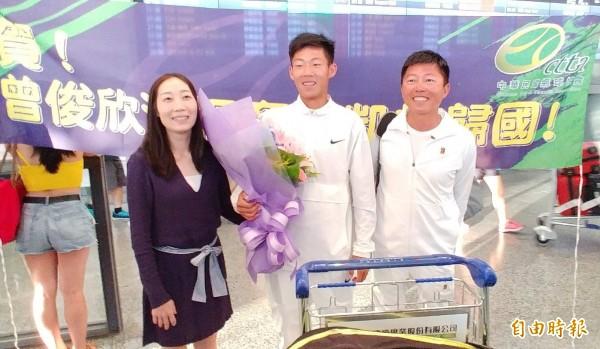 17歲「台灣之光」曾俊欣(中)傍晚搭機載譽歸國,父親曾育德(右)陪他在國外訓練比賽兩個多月,媽媽蔡仲涵(右)則在機場獻花迎接。(記者姚介修攝)