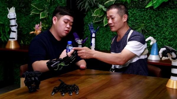 張憲良(右)赴馬來西亞為蔡一正(左)安裝義肢並指導操作。(成功大學提供)