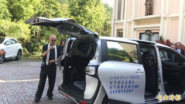 華光社福基金會董事長白正龍灑下聖水,替磊質庇護工坊獲國際扶輪所贈的新車祝聖、降福。(記者黃美珠攝)