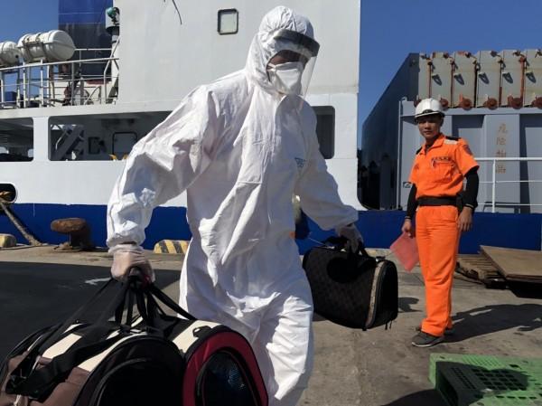 金門防疫人員將3袋裝有活體貓的袋子從船艙提上岸。(海巡署第12巡防區提供)