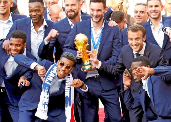 法國總統馬克宏(中排右)十六日在愛麗榭宮與凱旋歸來的本屆世界盃足球賽冠軍法國隊成員們合照,眾人留影俏皮畫面充分體現法國民族多元的社會現況。(路透)