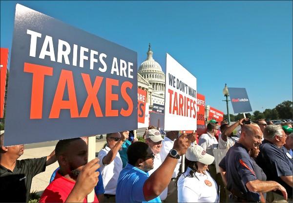 美國總統川普考慮加徵汽車關稅,汽車工人集會舉牌抗議,表示無助汽車業,還會削弱產業競爭力,造成失業問題。(法新社)
