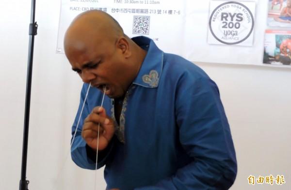 古威傑將繩子從鼻子進去、嘴巴拉出。(記者張菁雅攝)