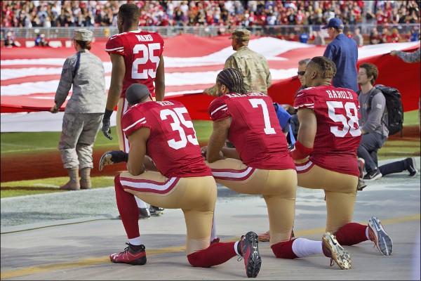 圖為前美國國家美式足球聯盟(NFL)「舊金山49人隊」四分衛卡佩尼克(背號七號)在二○一六年十一月六日與「紐奧良聖徒隊」(New Orleans Saints)比賽前,與隊友以單膝跪地方式表達抗議,當時場中正進行美軍官兵崇敬國旗的儀式,絕大多數人都起立致敬。  (法新社檔案照)
